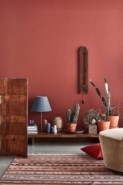 Ambiente decorado com tapete listrado, vasos de plantas e parede na cor damasco.